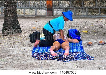 Bali,Indonesia-May 28,2010:Undentified tourist enjoying traditional local massages at Kuta Beach,Bali,Indonesia.This massages is very popular in Kuta beach among tourist.