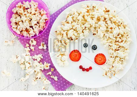Fun food art idea for positive food with popcorn and berries. Girl face from edible products on white plate. Children cooking concept top view
