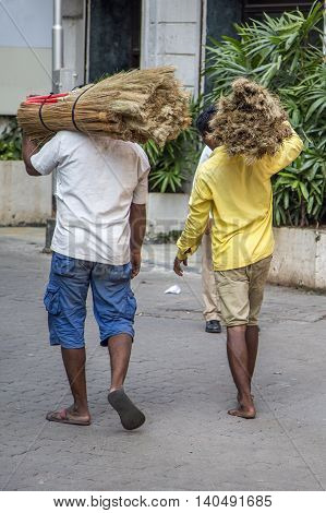 MUMBAI, INDIA - OCTOBER 9, 2015: Unidentified people carrying straw on the street of Mumbai India. With 12 million people Mumbai is the most populous city in India and the 9th most populous agglomeration in the world.