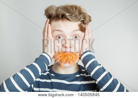 Goofy Young Boy With A Mouthful Of Carrot