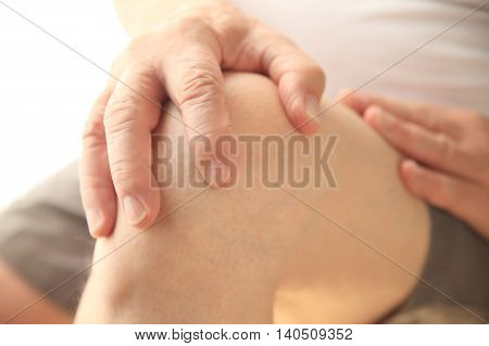 Senior man with a hand on his aching knee