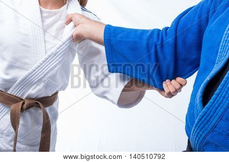Judo Gripping between female judo brown belt and her sensei black belt isolated on white background