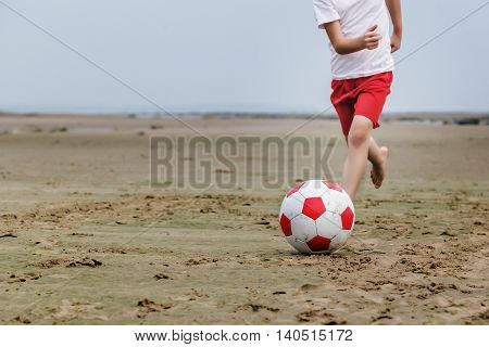 Child runs along the beach running for a soccer ball.