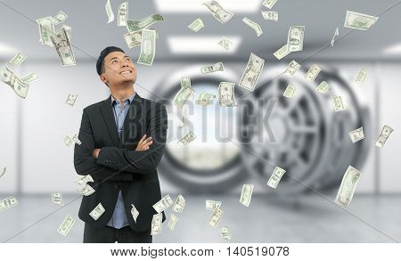 Businessman in suit standing in bank vault with hands folded smiling. Door open. City view seen through it. Dollar notes are falling at him. Concept of successful business idea implementation.