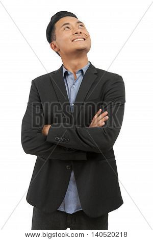 Asian man in formal black suit and blue shirt standing with folded hands looking up and smiling. Concept of business decision making. Isolated. Mock up