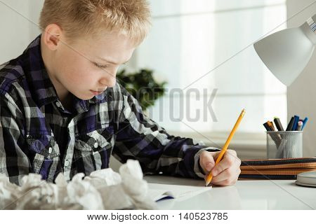 Young Teenage Boy Doing Homework At Desk In Home