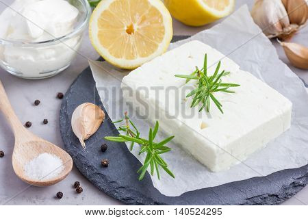 Ingredients for feta cream cheese rosemary lemon and garlic dip on slate board