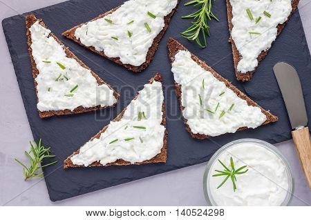 Pumpernickel bread with feta cream cheese rosemary lemon and garlic dip on slate board top view horizontal