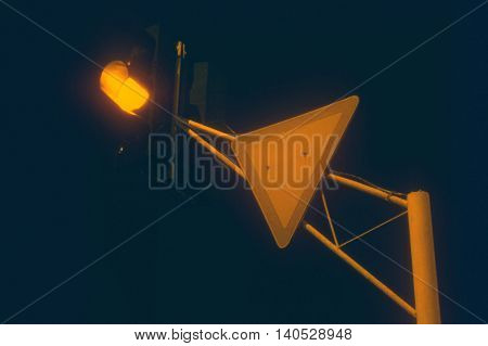 Traffic light in yellow light mode and give way sign in the night
