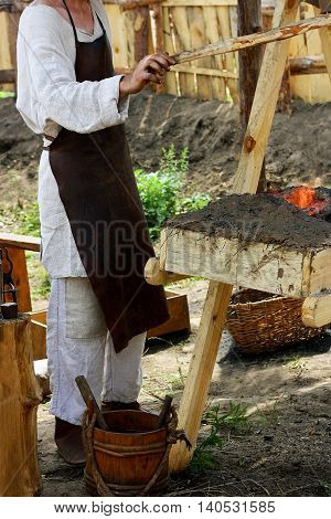 The male blacksmith in old clothes and apron is among the antiquities in the forge equipped for outdoor dining. With the help of special devices a person blows the fire in a makeshift horn.