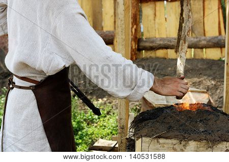 The male blacksmith in old clothes and apron is among the antiquities in the forge equipped for outdoor dining. With the help of special devices a person blows gets ticks from a homemade hearth items.