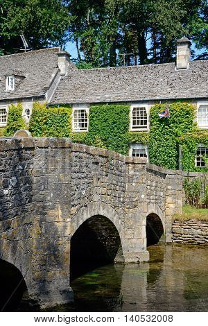 Pretty Cotswold stone bridge across the River Coln with The Swan Hotel to the rear Bibury Cotswolds Gloucestershire England UK Western Europe.