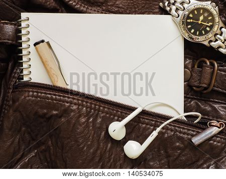 Notebook, pen, headphone and watch on a leather bag.