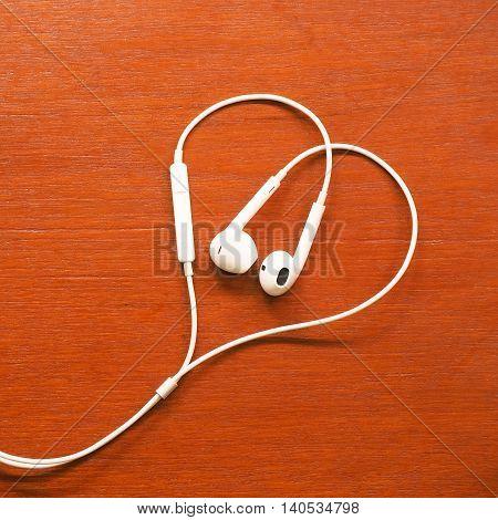 Headphone heart. Concept for valantine's day. White smalltalk on wood table.