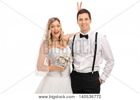 Blond bride pulling a bunny ears prank on the groom on the wedding photo isolated on white background