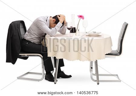 Desperate guy sitting alone at a restaurant table with his head down isolated on white background