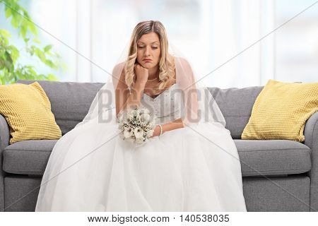 Depressed blond bride sitting on a sofa and looking down at home