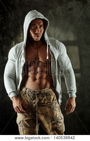 Bodybuilder posing in hoody, showing perfect abdominal muscle.