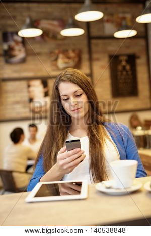 Young woman using mobilephone, sitting in cafeteria.