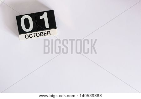October 1st. Day 1 of month, wooden color calendar on white background. Autumn time. Empty space for text.
