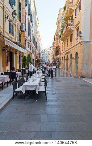 CORFU-AUGUST 22: Venetian architecture in Kerkyra city local restaurants invite tourists to have dinner on August 22 2014 on Corfu island Greece.