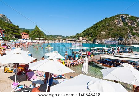 CORFU-AUGUST 26: Palaiokastritsa beach with crowd of holidaymakers sunbathing on the beach August 262014 on Corfu Greece. Palaiokastritsa is a village with famous beaches in the North West of Corfu.