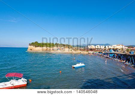 Sidary sandy beach people sunbath on the shore. Corfu Greece.