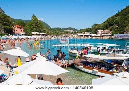 CORFU-AUGUST 26: Palaiokastritsa beach with crowd of people sunbathing on the beach August 262014 on Corfu Greece. Palaiokastritsa is a village with famous beaches in the North West of Corfu.