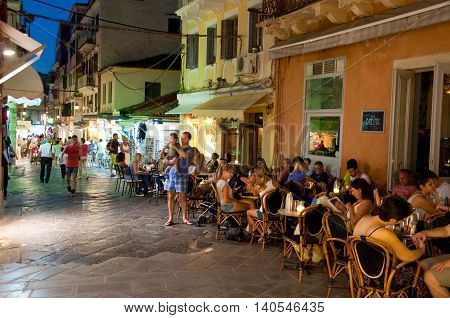 CORFU-AUGUST 25: Tourists have dinner in a local restaurant on August 25 2014 in Kerkyra town on the Corfu island Greece. Kerkyra is a town on the island of Corfu in the Ionian Sea Greece.