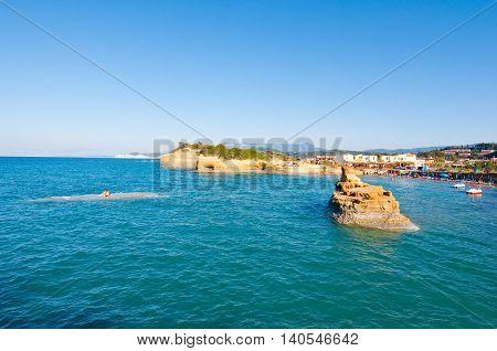 Famous Sidary beach people sunbath on the a sandy shore. Corfu Greece.