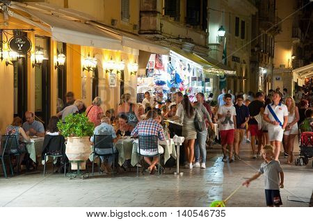 CORFU-AUGUST 25: Tourists have dinner in a local restaurant on August 25 2014 in Kerkyra town. Corfu Greece.