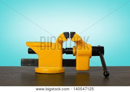 The metalwork tool - Yellow with black a vise on a wooden table and a blue background.