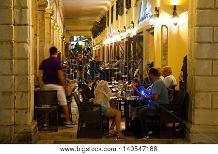 CORFU-AUGUST 25: Tourists have their meal in a local restaurant on August 25 2014 in Kerkyra town on the Corfu island Greece.