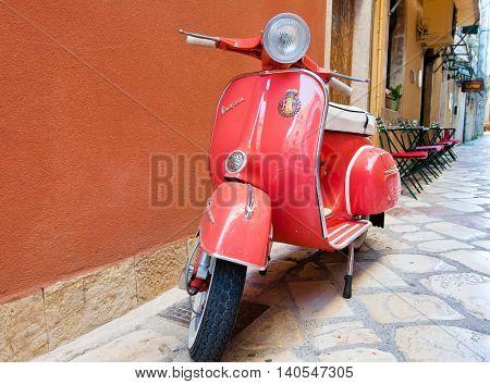 CORFU-AUGUST 22: Classic Vespa scooter on Kerkyra street on August 22 2014 on Corfu island. Greece. Vespa is an Italian brand of scooter manufactured by Piaggio.