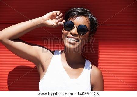Outdoor portrait of young attractive African American with cheerful and carefree look smiling showing her white teeth wearing stylish sunglasses and white tank top against red wall background poster