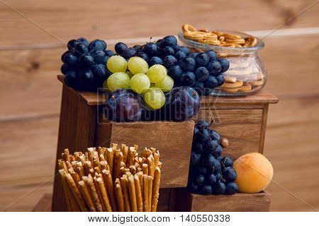 fresh fruits and berries plums, grapes on a wooden stand and crispy breadsticks in glass jars standing on the wedding Welkom
