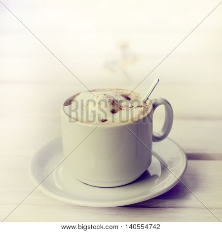 frothy cappuccino with cinnamon in a white mug and spoon / retro coffee
