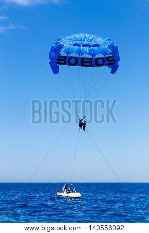 HURGHADA EGYPT - MAY 20: Parasailing in a blue sky near sea beach at May 20 2015 in Hurghada Egypt. Parasailing is a popular recreational activity among tourists in Egypt.