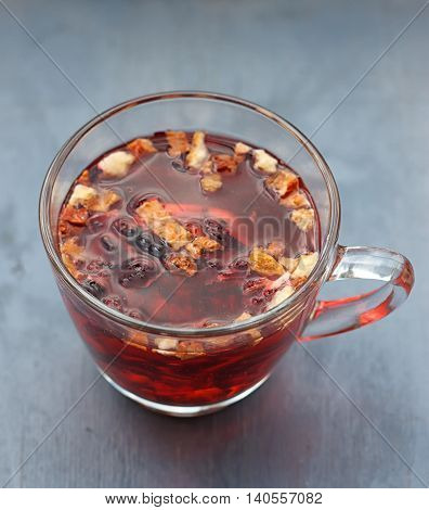 Red fruit tea in transparent glass Cup on a wooden table