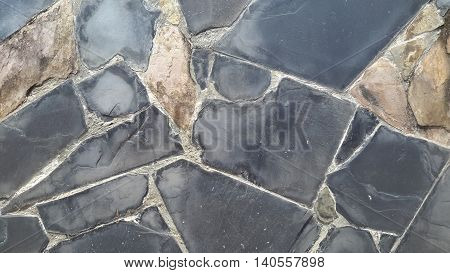 gray and brown, smooth and rough, quadrilateral shapes seen in stone vaneer siding on a concrete wall, Songkhla, Thailand