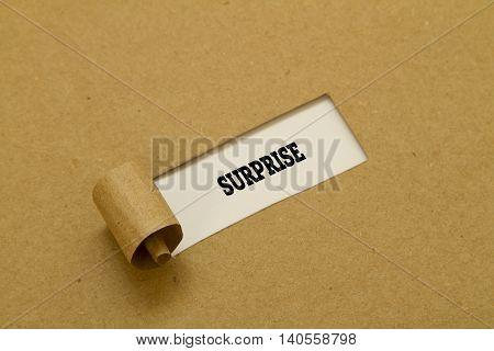 SURPRISE word written under torn paper .