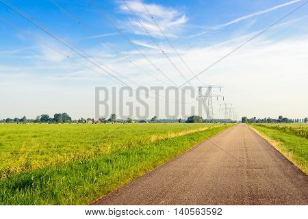 Seemingly endless narrow asphalt road in a rural area with a long line of power pylons connected to high voltage wires. It's summer the sky is blue with white clouds and contrails.