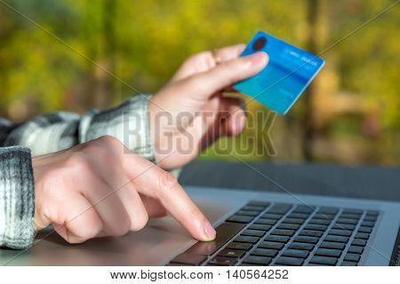Hands of person entering credit Card Data on Laptop Computer Internet shopping or booking Cup of Coffee on wooden background