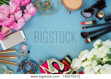 styled feminine desktop - woman fashion flat lay items and fresh flowers on blue wooden background, copy space, top view