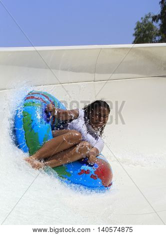 Rhodes Greece-July 26 2016:Black cheerful girl drive with tube on the rafting slide in the Water park.Rafting slide is one of many popular game for adults and children in park.Water Water Park is located on the island of Rhodes in Greece and on