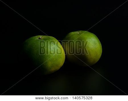 Oranges on a black background .The light from the right of the image