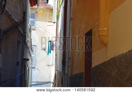 typical narrow alley way in france with clothelines