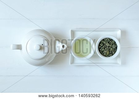 Green tea in tea pot and white cups top view