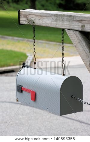 Rural mailbox swinging on steel chains to prevent vandals from knocking it off the post.