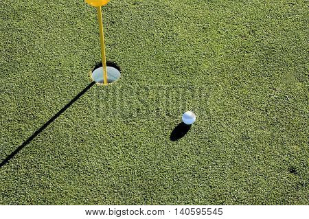 Golf hole showing ball mark and golf ball next to hole.